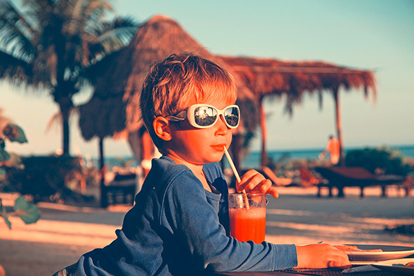 little boy drinking watermelon juice on tropical beach
